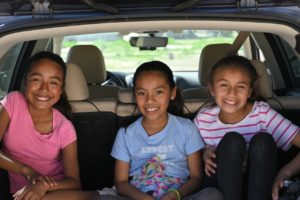 three girls sitting in the back of a car during a fun road trip